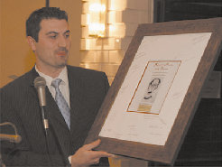 Alumni and Friends President Arakel Arisian presenting framed cover of the Festschrift in honor of Dickran Kouymjian.