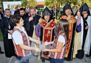 Archbishop Hovnan Derderian, center, and Archbishop Moushegh Mardirossian, right, bless soil held by Zareh Apkarian and Sevana Wassilian of the Keyan Armenian School.